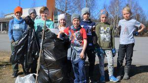 Ett tiotal barn poserar med sopsäckar och ser glada ut.