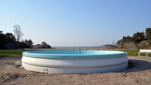 En tom bassäng på en strand. Hav i bakgrunden.