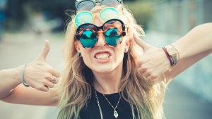 En tjej med långt lockigt hår bär tre olika par solglasögon och håller två tummar upp mot kameran med en stor grimas.