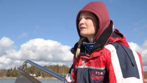 Sandra Blomqvist styr en öppen båt med en strandkant i bakgrunden