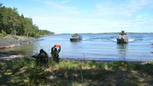 två militärer på land signalerar till båt