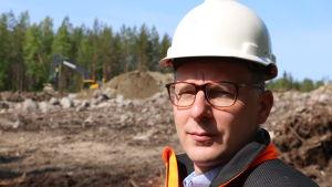 En man med glasögon och vit hjälm på huvudet står vid ett markarbete. I bakgrunden skymtar en grävmaskin.