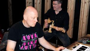 Valokuva bändistä miksauspöydän ääressä studiossa.