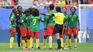 En domare försöker få Kameruns damlandslag att fortsätta matchen.