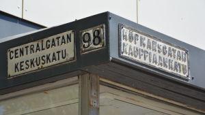 En bild på tre slitna gatuskyltar på en vägg. På en står det centralgatan en annan nummer 98 och en tredje köpmansgatan