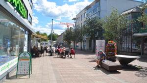 En bild från köpmansgatan i Karis. Människor sitter vid bord på gatan på en uteservering. En man sitter på en bänk och bakom honom finns blomdekorationer.
