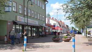 En bild från Köpmansgatan där det syns människor gå på gatorna och hus längs med vägen.