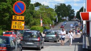 En bild på en väg i Karis centrum. På bilden syns bilar som står parkerade och människor som går längs vägen.