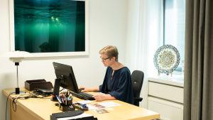 Krista Mikkonen työpöytänsä ääressä.