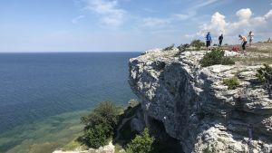 Mänskor uppe på en hög kalkstensklippa med utsikt över havet.