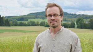 En man står i en beige skjorta. I bakgrunden syns åkrar och skog.