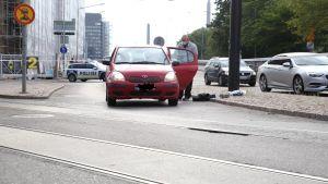 En röd bil som står tillbucklad mitt på Sandviksgatan, och en polis som undersöker den.