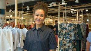 En ung leende, tjej står framför olika kläder som hänger i butiken.
