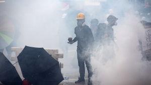 Demonstrant i Hongkong iförd gasmask och gul skyddshjälm står mitt i ett moln av tårgas.