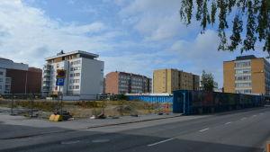 Byggnadsområde i vasa. I förgrunden ett urgrävt område för ett nytt hus. I bakgrunden en rad med bostadshus.