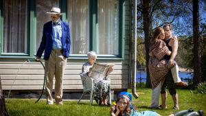 En familj i flera generationer på en gräsmatta framför en sommarvilla.