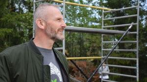 En man med skägg och gråsprängt hår följer med ett husbygge.