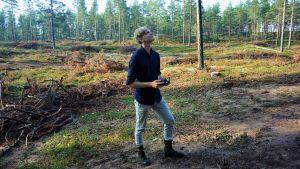 Ung man står och håller en fjärrkontroll för en drönare i skogen.