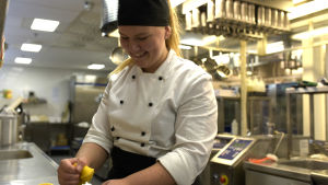 Kvinnlig kock pressar citronjuice.