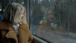 En ung flicka sitter och tittar ut genom ett bussfönster.