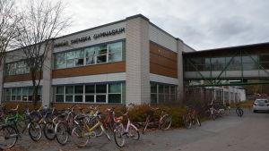 Pargas svenska gymnasiums byggnad i ljusa och bruna tegel, med cyklar parkerade utanför.