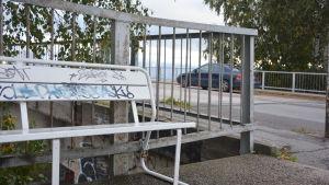 En vit bänk med graffiti vid ett brostängsel och en bil i bakgrunden.
