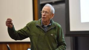 En gammal man står med handen höjd eftersom han förklarar någonting. Han har glasögon och en grön skjorta.