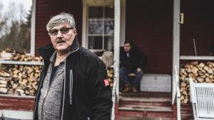 Mies seisoo talon edessä, katsoo kameraan. Talon portailla istuu toinen mies.