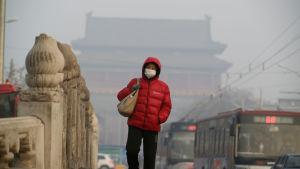 En kvinna går över en bro i Peking iklädd en ansiktsmask på grund av den förorenade luften.