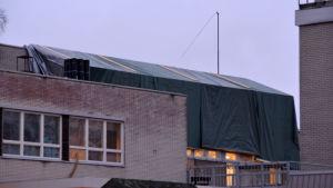 Presenningar täcker taket som brann.