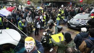 Gula västarna har än en gång gått ut på gatorna i Paris. En del håller i franska flaggor.