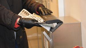 Tidningar sätts i en postlåda.
