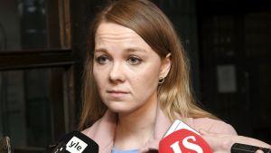 Katri Kulmuni, en ung kvinna med blont hår och en rosa jacka blir intervjuad framför en mörk vägg. I förgrunden syns två stycken stora mikrofoner och ett par ljudinspelare.