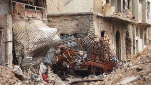 Kuorma-auto ja rauniot pommitusten jäljiltä Syyrian Homsissa