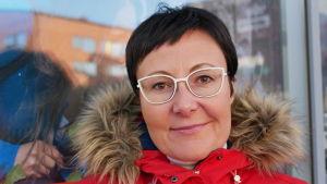 Närbild på Visit Rovaniemis VD utanför kontoret. Hon har röd jacka, svart kort hår och glasögon med vita bågar.