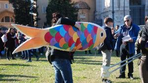 En person som bär på en färgglad sardinmodell.