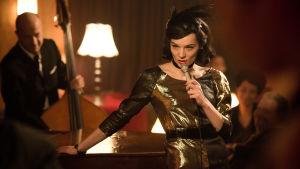 Nainen laulamassa klubilla pöytään nojaten.