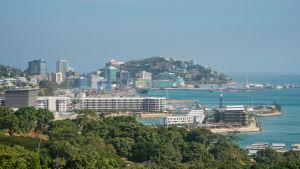 Kaupunkimaisema Port Moresbystä, etualalla puita.