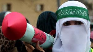 Nainen kasvot silmiä lukuunottamatta peittävässä huivissa ja Hamasin otsanauhassa pahvinen ohjus kädessään.