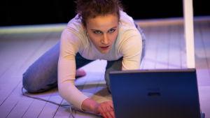 En ung kvinna står på armbågar och knän på golvet och tittar in i en datorskärm.
