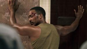 Mies kädet seinällä, otsalla verta