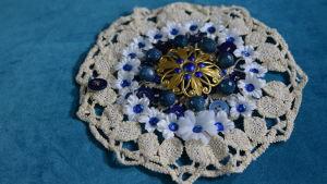 Ett stort armband av en återvunnen virkad duk med vita tygblommor, blåa paljetter, knappar och pärlor.