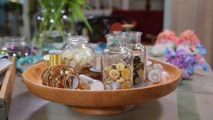 Ett brunt träfat med små glasburkar fyllda med ljusa knappar, guldiga paljetter och metalltråd.