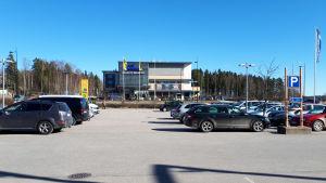 En parkeringsplats med bilar framför en affär. En person går förbi längre bort.