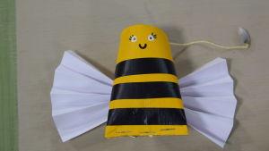 Ett handgjort leksaksbi, gjord av en tom pappersrulle.