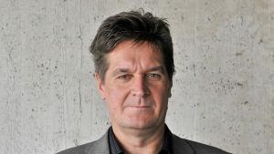 Närbild på Juhani Ruohonen som har mörkt hår och en grå kavaj.