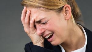 gråtande blond kvinna lutar ansiktet mot handflatan
