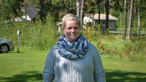 En leende kvinna i grå stickad tröja står på en gräsmatta.