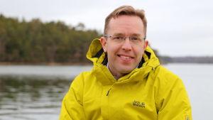 Ilari E. Sääksjjärvi istuu merenrannalla.