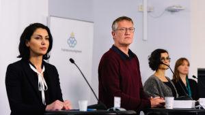 Anders Tegnell och andra personer står framför talarpodier och mikrofoner under en presskonferens.